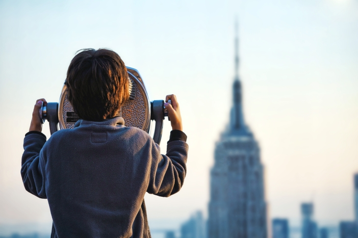 child looking through binoculars in NYC