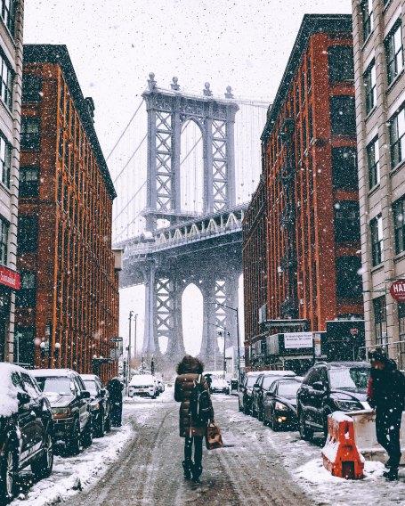 person walking in snow in Brooklyn New York towards Brooklyn Bridge
