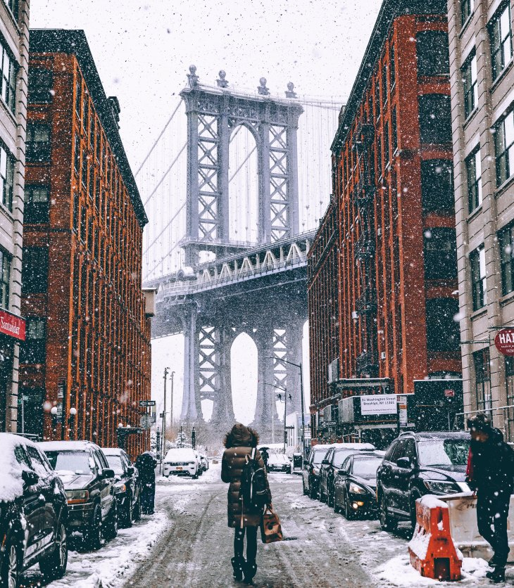 person walking in snow in Brooklyn New York towards Brooklyn Bridge