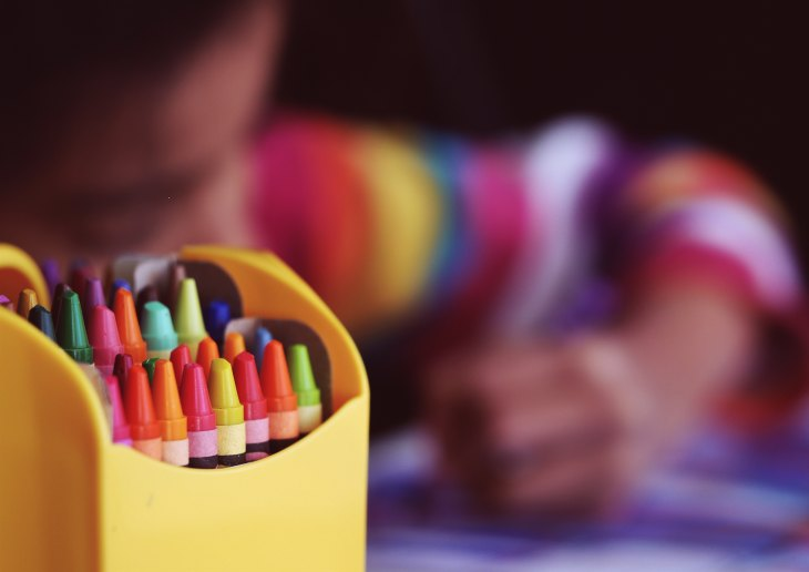 pre-school boy drawing with crayons