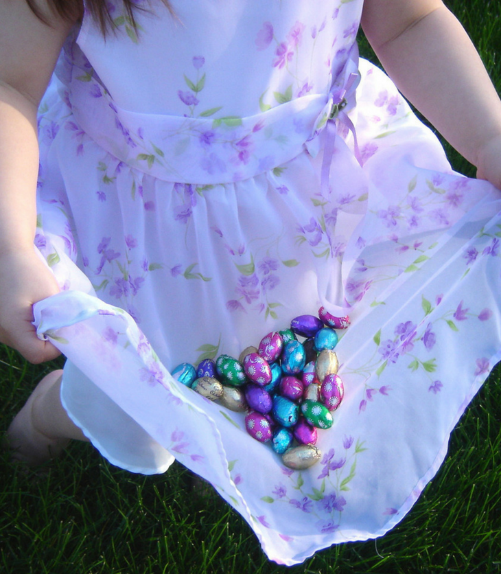 little girl collecting Easter eggs at Easter egg hunt