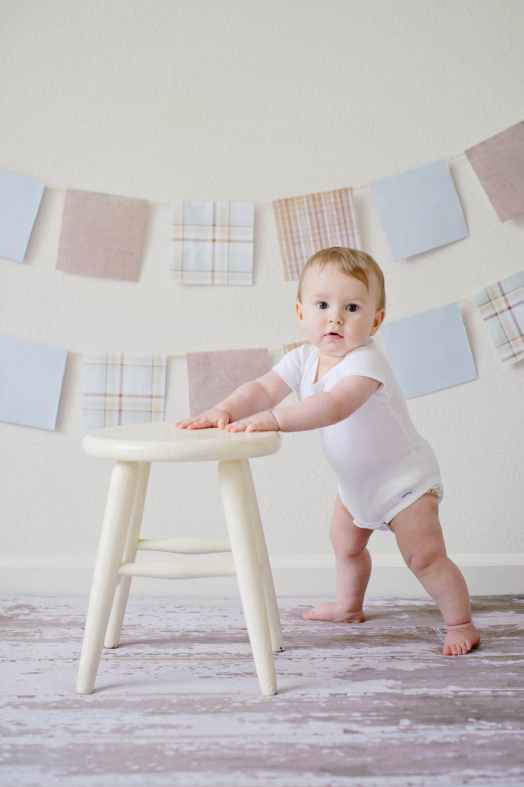 photo of baby standing at a chair