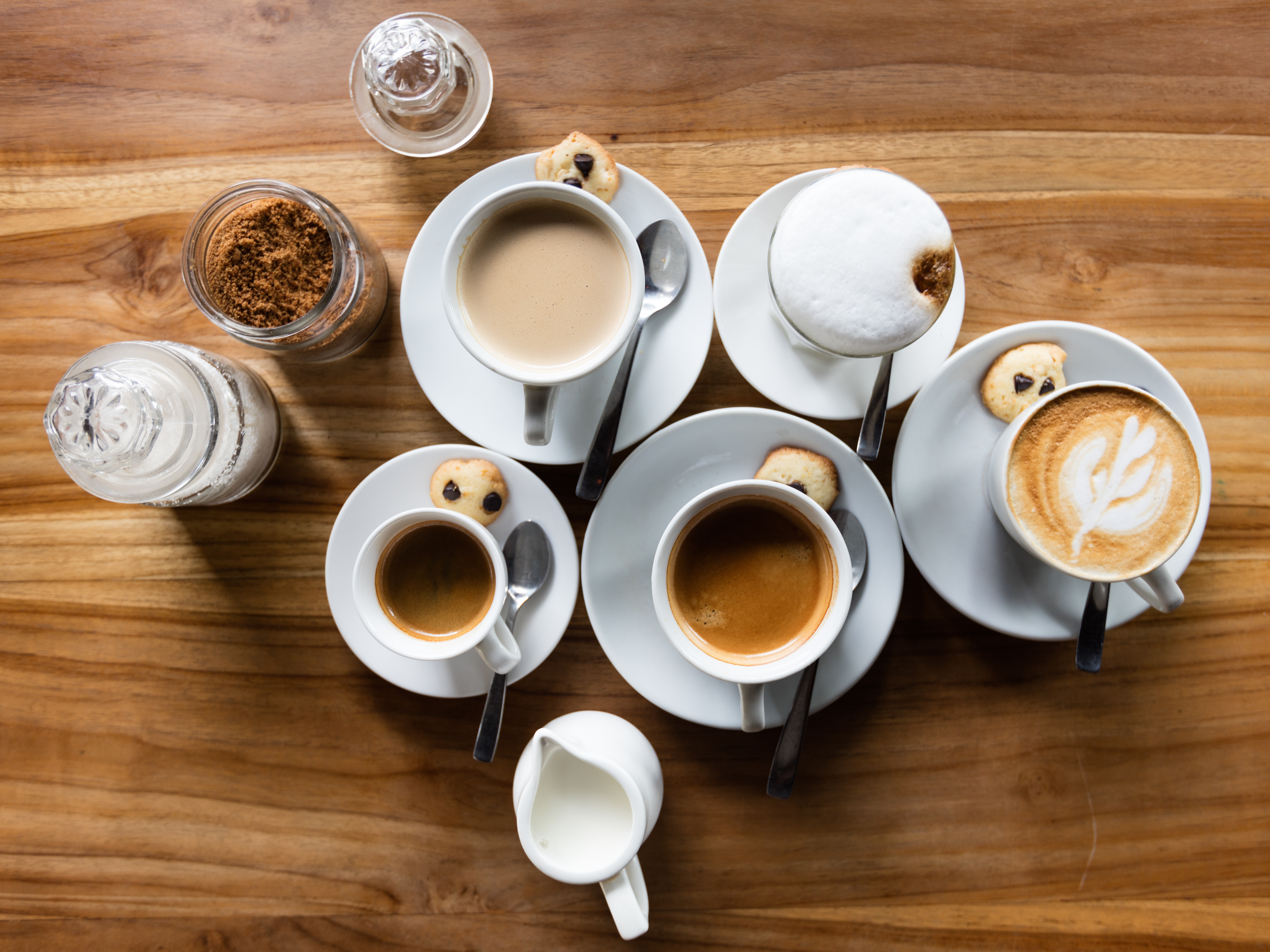 An overhead shot of five white cups with various kinds of coffee