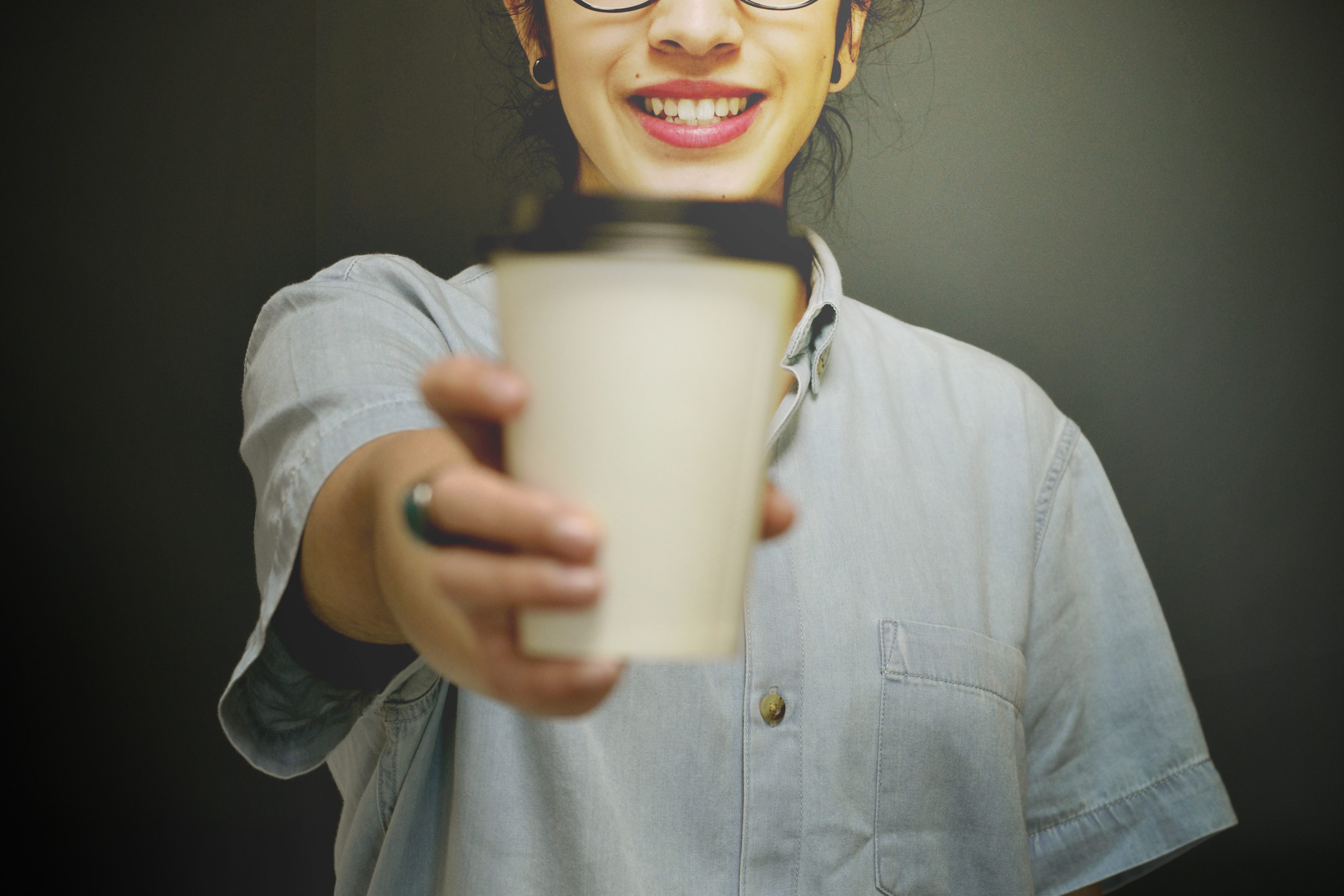 A smiling woman holding out a coffee cup