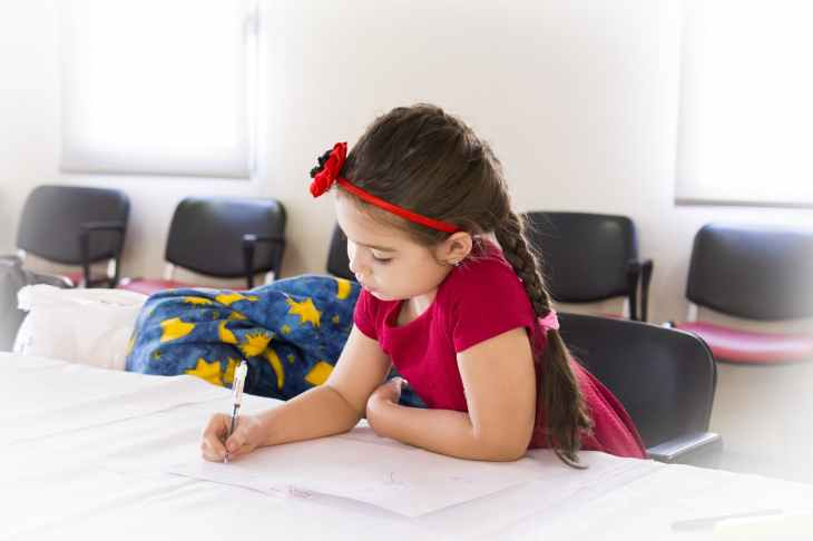 girl in red short sleeve dress and flower headband holding pen and writing on paper on table