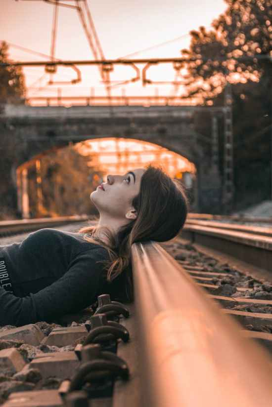selective focus photography of woman lying on train rail during golden hour