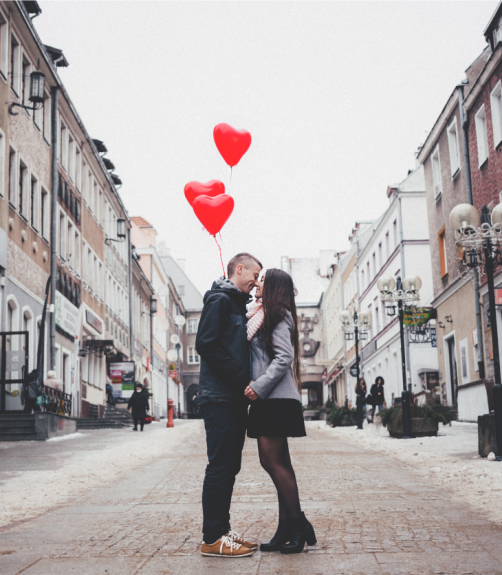 couple walking in city kissing and holding red heart balloons
