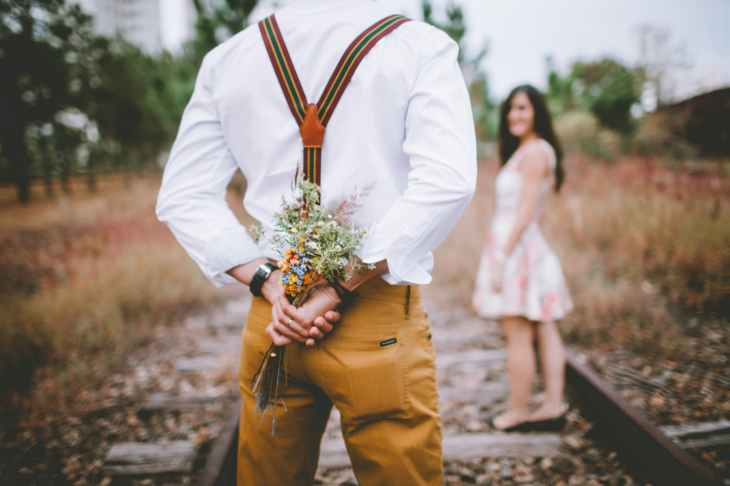 man holding flowers standing near woman