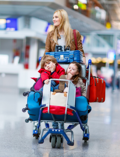 mother pushing a cart with children, kids and suitcases at the airport