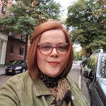 Australian woman with glasses in Park Slope Brooklyn walking down street with trees