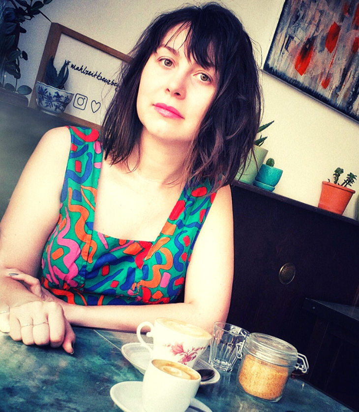 Australian woman in Brooklyn coffee shop cafe with cup of coffee