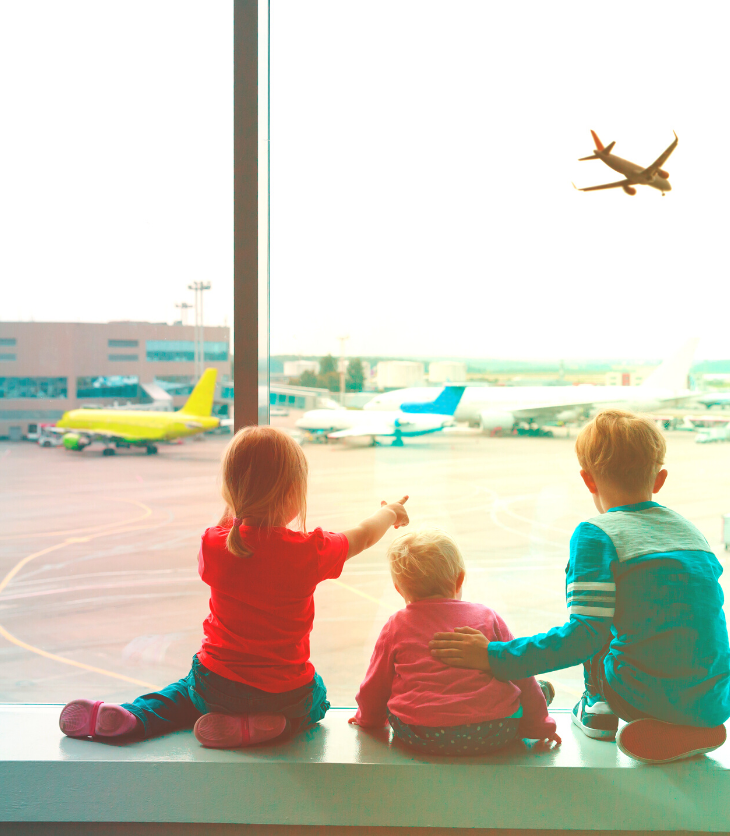 kids at airport looking at airplane