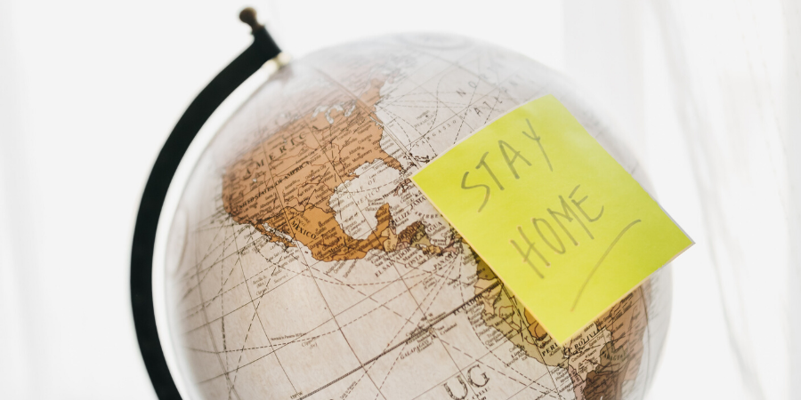 world globe with post it note saying stay home