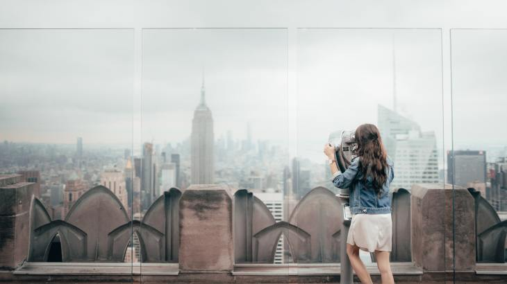 woman standing on building in New York looking at Empire State Buiilding