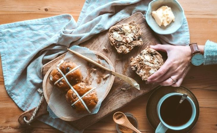 Easter hot cross buns on a plate and wooden cutting board with butter and someone holding one and a cup of coffee nearby