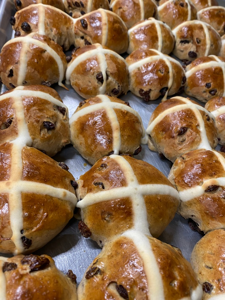 tray of Easter hot cross buns with raisins and cross.