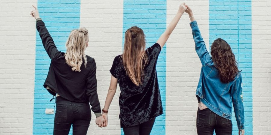 three women holding hands and putting them in the air in front of a brick wall with blue and white stripes